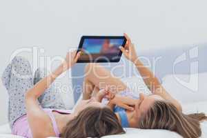 Friends wearing pajamas holding tablet