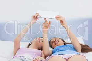 Girls holding tablet and lying in bed