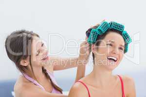 Girl fixing her friends hair rollers