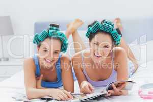 Girls in hair rollers holding magazines
