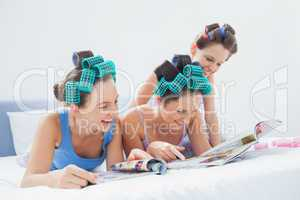 Girls wearing pajamas and hair rollers sitting in bed with magaz