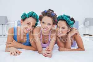 Girls in hair rollers lying in bed