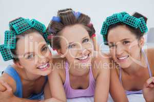 Friends in hair rollers and pajamas lying in bed