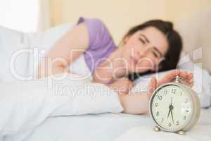 Upset girl in her bed turning off her alarm clock