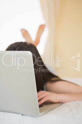 Laptop covering girls face on bed