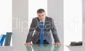 Frowning businessman standing in front of a desk