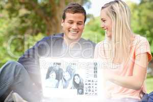 Smiling young couple watching photos together on digital interfa