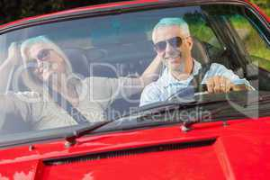 Happy mature couple in red cabriolet