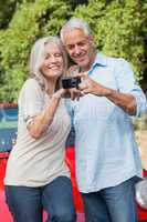 Smiling mature couple looking at pictures on their camera