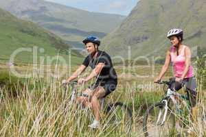 Athletic couple biking through countryside