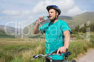 Fit man leaning on his mountain bike drinking water