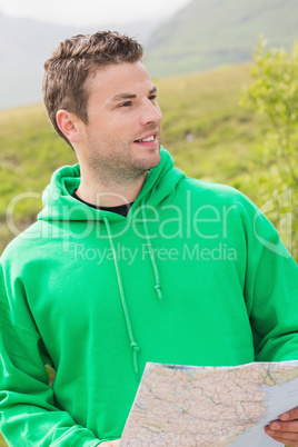 Athletic man holding a map and looking ahead