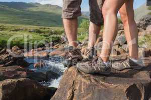 Couples feet standing at edge of river