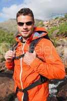 Man wearing rain jacket and sunglasses smiling at camera