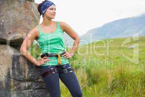 Pretty female rock climber leaning on rock face