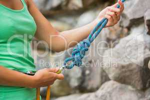 Female rock climber adjusting harness