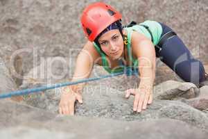 Determined girl climbing rock face