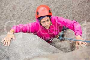 Smiling girl climbing up rock face