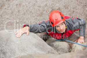 Determined man climbing rock face