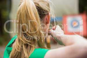 Rear view of blonde about to shoot arrow