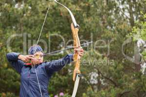 Concentrating brunette practicing archery