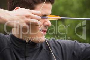 Concentrated man practicing archery