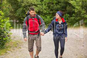 Smiling couple going on a hike together holding hands