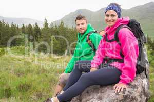 Couple sitting on a rock resting during hike