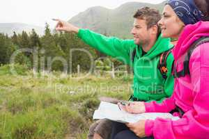 Couple sitting on a rock during hike using map and compass