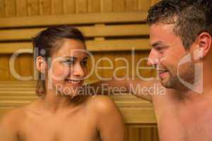 Cheerful couple relaxing in a sauna and chatting