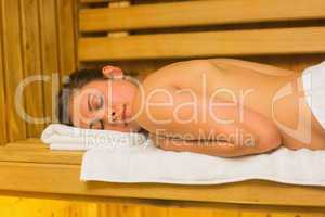 Calm brunette lying down in a sauna
