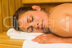 Smiling brunette lying down in a sauna
