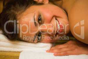 Happy brunette lying in a sauna looking at camera