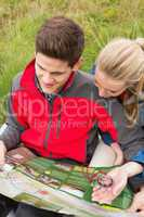 Cheerful couple taking a break on a hike to look at map and comp