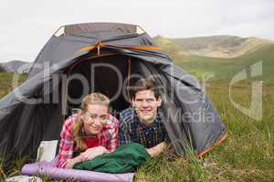 Happy couple lying in their tent after a hike and looking at cam