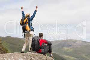 Excited couple reaching the top of their hike