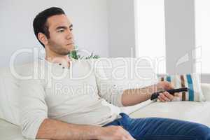 Serious man holding remote control