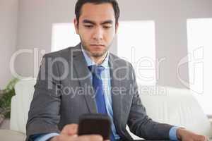 Serious businessman sending a text message