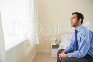 Unsmiling man looking out the window sitting on his bed