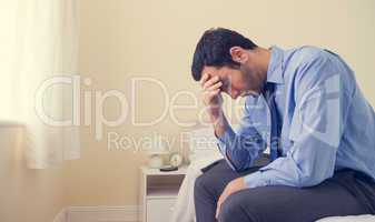 Depressed man sitting head in hands on his bed