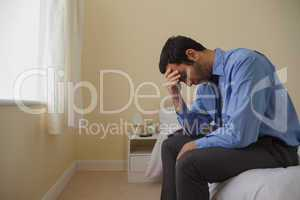 Mournful man sitting head in hands on his bed