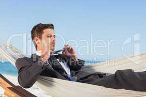 Businessman man lying in hamock taking off his tie