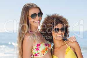 Two friends wearing sunglasses on the beach and smiling