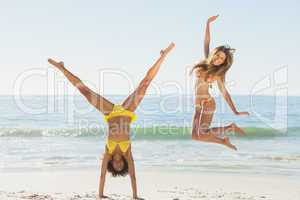 Friends in bikinis jumping and doing handstand