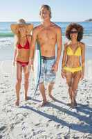 Three friends walking down on beach