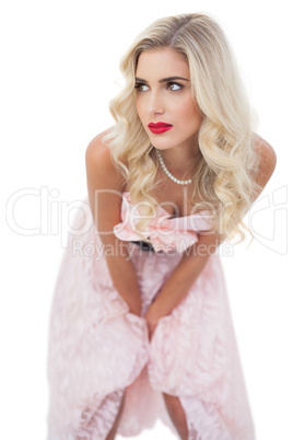 Thinking blonde model in pink dress posing hands on the thighs