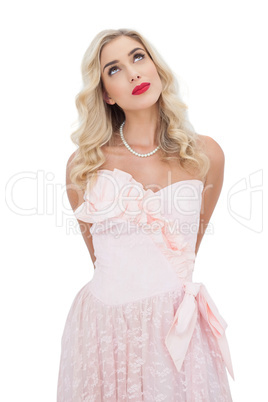 Thinking blonde model in pink dress posing looking away