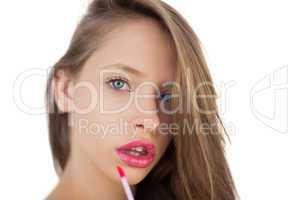 Serious brunette model applying pink gloss on her lips