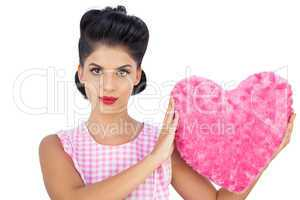 Unsmiling black hair model holding a pink heart shaped pillow