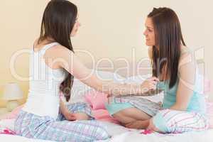 Girls in pajamas talking on bed